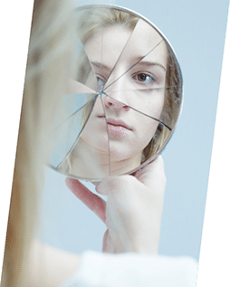 Person looking into shattered mirror